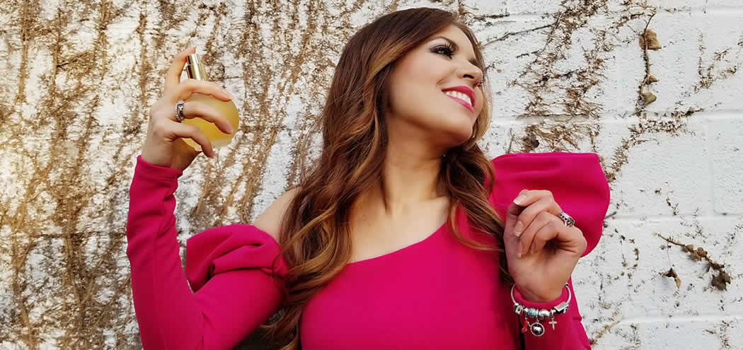 beauty influencer perla lopez baray holding a bottle of perfume